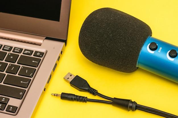 ラップトップ、青いマイク、黄色の表面にマイクを接続するためのコード。音楽トラックを録音するための機器。