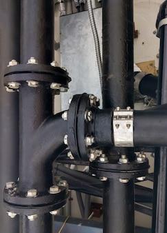 Большая черная стальная труба с тройником в точке соединения вентиляционной системы для использования на сложном виде спереди больницы для копировального пространства.