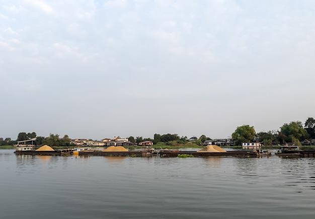 Большой грузовой катер, загружающий много песка, курсирует по большой реке для транспортировки на строительную площадку недалеко от бангкока, таиланд, вид спереди для копии пространства.