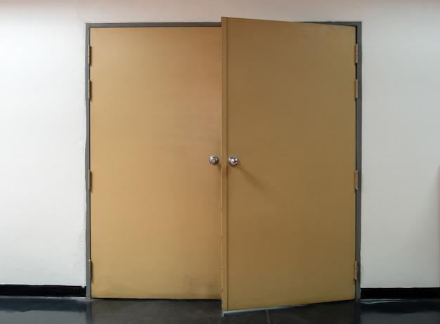 誰かがオフィスのファイリングルームに入った後、大きな金属製のドアは半開きのままにされ、金属製のドアの周りの人々を空にしました。コピースペースの正面図です。