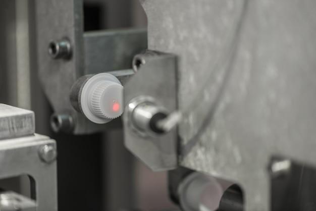 レーザーは、コンベヤーのプラスチックカバーから情報を読み取ります。工場でのボトルキャップ