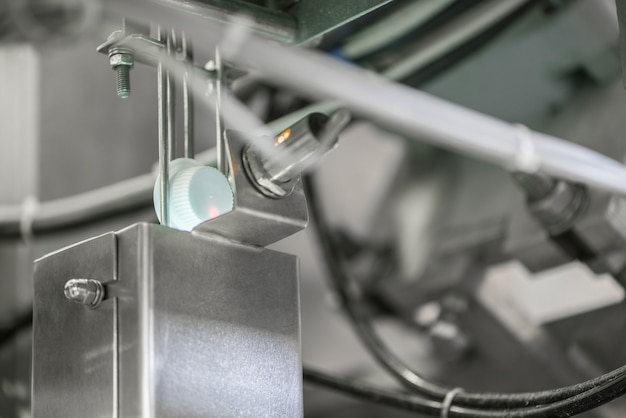 Лазер считывает информацию с пластиковой крышки конвейера. крышки от бутылок на заводе