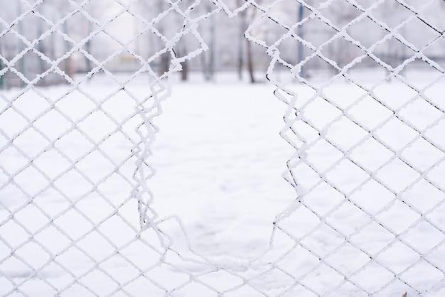 Решетчатый забор засыпан снегом. зимнее время. сильный снегопад и лед.
