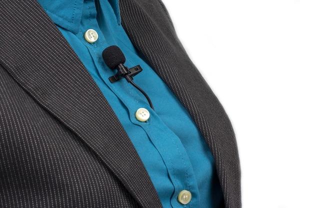 Петличный микрофон закреплен зажимом на синей женской рубашке крупным планом. аудиозапись звука голоса на конденсаторном микрофоне.