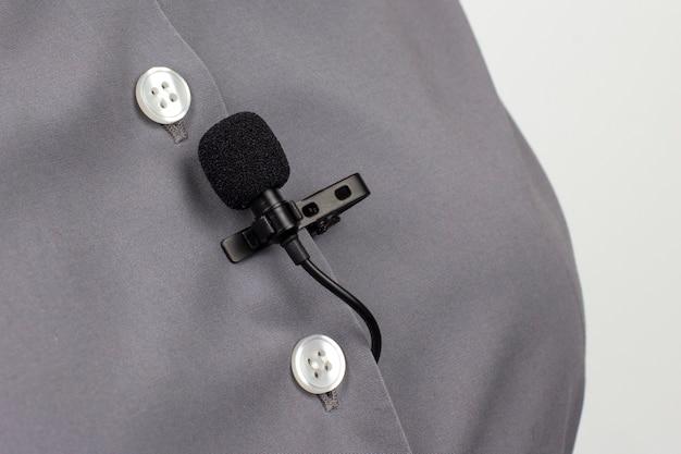 Петличный микрофон закреплен зажимом на серой женской рубашке крупным планом. аудиозапись звука голоса на конденсаторном микрофоне.