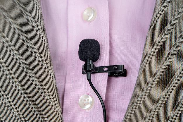 Петличный микрофон закреплен зажимом на крупном плане женской рубашки. аудиозапись звука голоса на конденсаторном микрофоне.