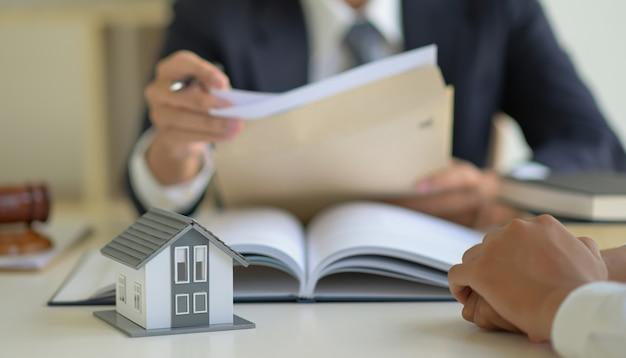 변호사는 주택 구입 계약에 대해 고객과 상담하고 있습니다.