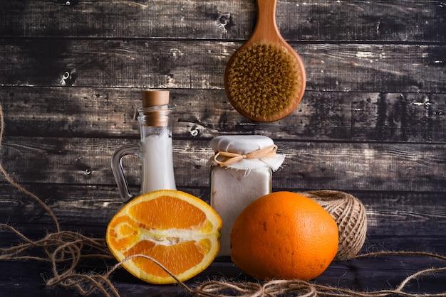 어두운 나무 배경에 바디 케어 제품으로 평신도 구성. 천연 크림 한 병, 코코넛 오일 한 병, 잘 익은 오렌지