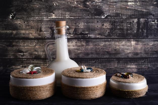 어두운 나무 배경에 바디 케어 제품으로 평신도 구성. 천연 크림 한 병과 코코넛 한 병