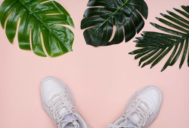 Красота макета. белые кроссовки, зеленые пальмовые листья и белый планшет. вид сверху на белом фоне