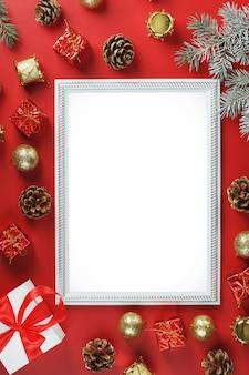Макет рамки со свободным белым пространством на красной стене и елочными украшениями.