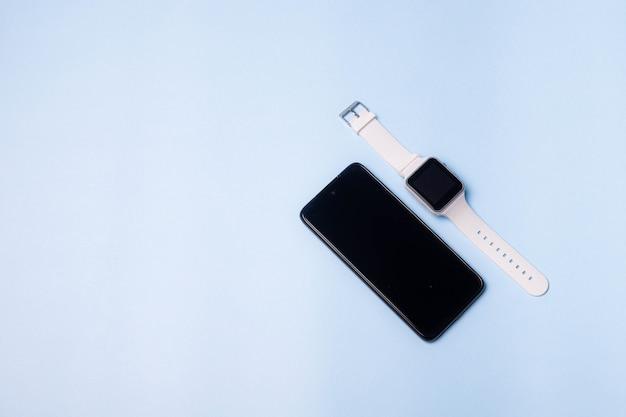 파란색 배경에 시계와 휴대 전화의 레이아웃. 가전 제품 및 전자 제품. 현대 가제트. 전화 헤드폰 시계. 사업. 학생. 무선 헤드폰. 만보계로 시계. 공간 복사