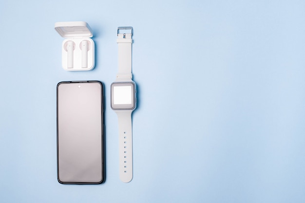 Раскладка часов и телефона на синем фоне. техника и электроника.