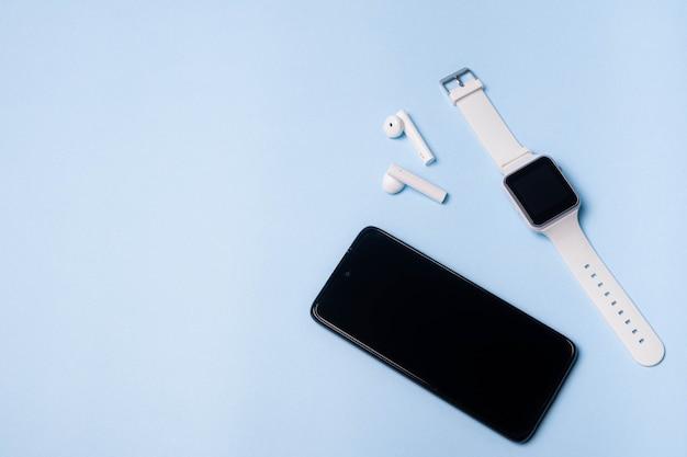 青い背景の時計と携帯電話のレイアウト。電化製品および電子機器。