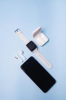 파란색 표면에 시계와 휴대 전화의 레이아웃. 가전 제품 및 전자 제품.