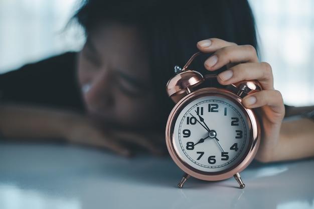 Ленивая азиатка легла на стол и потянулась, чтобы выключить будильник.