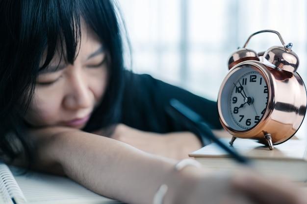 게으른 아시아 여자는 알람 시계와 함께 테이블에 누워