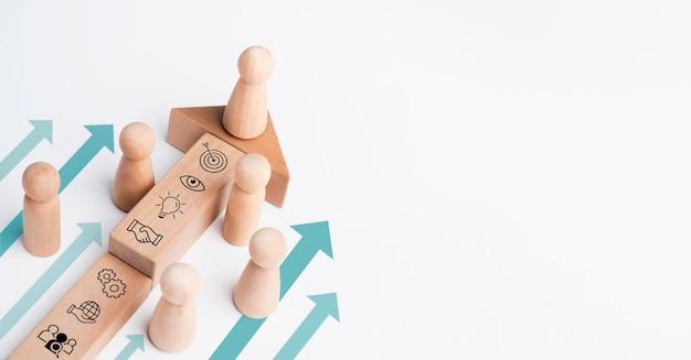 Лидер, деревянная фигура, ведущая команду с бизнес-значком на деревянном блоке со стрелками заголовка на белом фоне с копией пространства. бизнес-стратегия с процессом успеха роста, концепция лидерства.