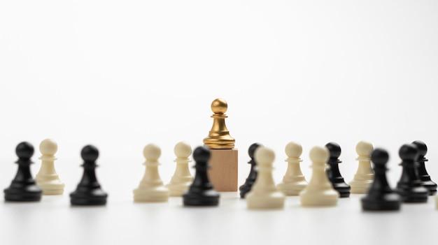 ボックスの上に立っているゴールデンチェスのポーンのリーダーシップは、影響力とエンパワーメントを示しています。リーダーチーム、成功した競争の勝者、戦略を持つリーダーのためのビジネスリーダーシップの概念