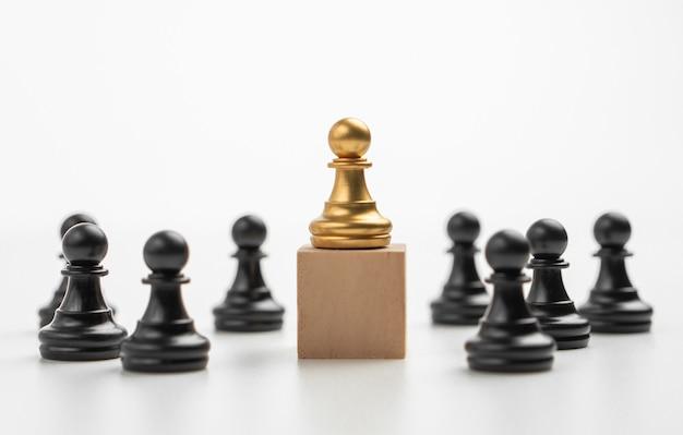 ボックスの上に立っているゴールデンチェスのポーンのリーダーシップは、影響力とエンパワーメントを示しています
