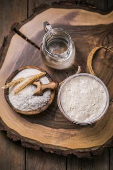 パンのパン種が活発です。パン焼きのパン種として使用する水と小麦粉のスターターサワードウ発酵混合物。 Premium写真