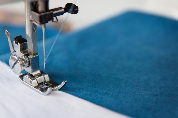 바늘로 재봉틀의 다리가 파란색 천을 꿰매다 매크로 전면 보기