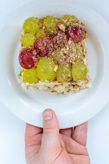 伝説的なティファニーのレイヤードサラダ。白地にブドウ、チキン、チーズを添えています。サラダのレシピを料理ポータルに投稿した女性のニックネームにちなんで名付けられました。