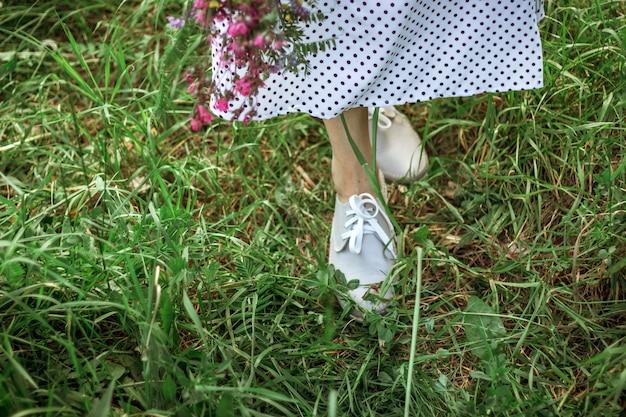 Ноги красивой девушки в длинном белом платье и серых туфлях стоят в высокой зеленой траве. девушка держит букет фиолетовых полевых цветов. выборочный фокус. копировать пространство.