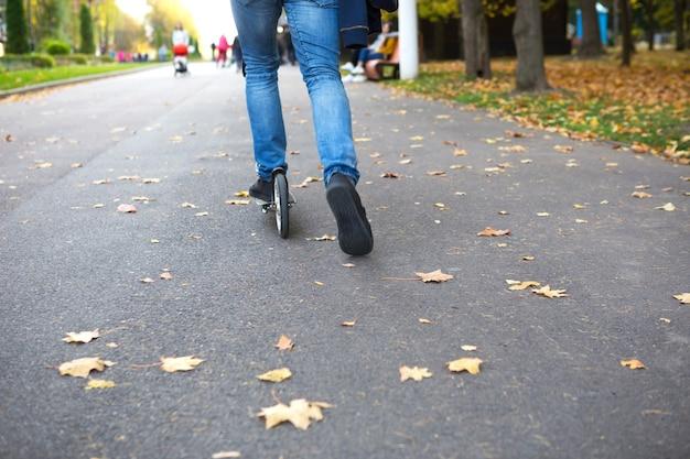 Ноги человека в джинсах и кроссовках на скутере в парке осенью с опавшими сухими желтыми листьями на асфальте. осенние прогулки, активный образ жизни, экологичный транспорт, пробки