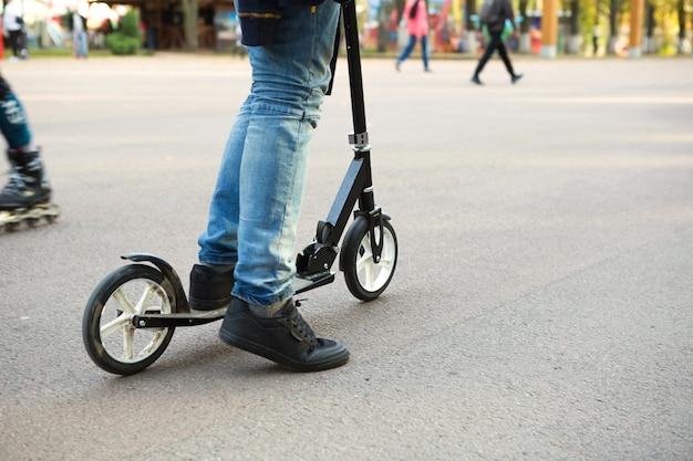 아스팔트 트랙에 있는 공원에 있는 스쿠터에 청바지와 운동화를 신은 남자의 다리. 스포츠 걷기, 건강한 활동적 라이프스타일, 친환경 교통, 교통