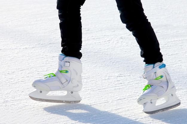 아이스 링크에서 스케이트를 타는 남자의 다리. 스포츠 및 엔터테인먼트. 휴식과 겨울 방학.