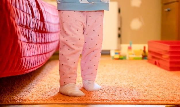 小さな子供の足が部屋の中を歩き回っています。赤ちゃんの最初のステップの概念。顔なし。幸せな親子関係