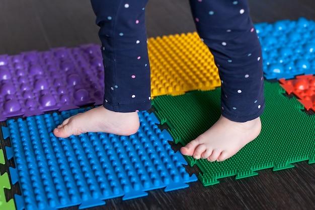 Ножки маленького ребенка на ортопедических ковриках.