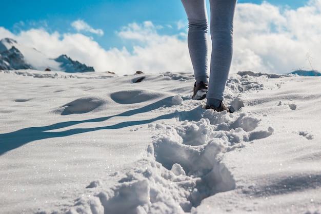 깊은 눈 속에서 겨울 신발을 신고 있는 젊은 여성의 다리. 파란 하늘.