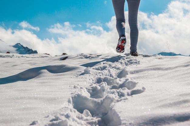깊은 눈 속에서 겨울 신발을 신고 있는 젊은 여성의 다리. 눈 산 정상입니다.