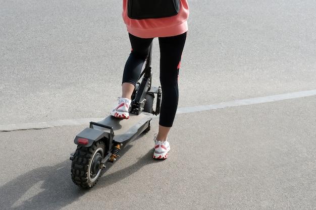 도시 아스팔트 위에 검은 전기 스쿠터를 타는 흰색 운동화와 체육관 레깅스를 입은 알 수없는 소녀의 다리. 현대 교통, 전기 킥 스쿠터.