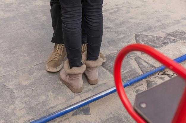 抱きしめるティーンエイジャーの足はアスファルトの上にあります。思春期の関係の概念