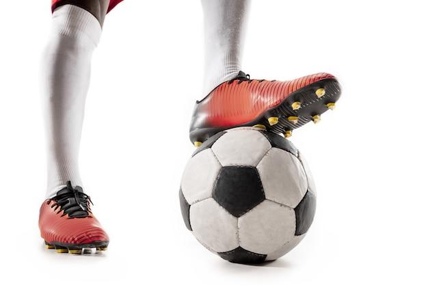 白で隔離のサッカー選手のクローズアップの脚。動作中またはボールを持った動きのアフリカ系アメリカ人モデル。サッカー、ゲーム、スポーツ、プレーヤー、アスリート、競争の概念