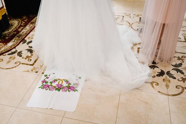 Ноги жениха и невесты становятся на вышитое полотенце, традиционно на свадебной церемонии в церкви. появляются снизу до ног.