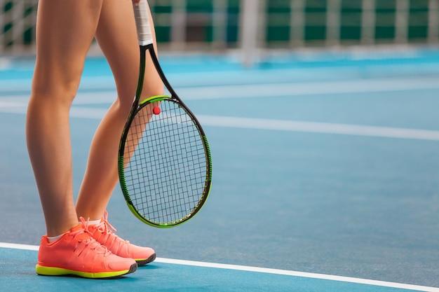 ラケットと閉じたテニスコートで若い女の子の足