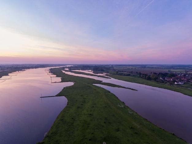 네덜란드의 아름다운 일몰 동안 에버 딩겐 마을로 둘러싸인 렉 강