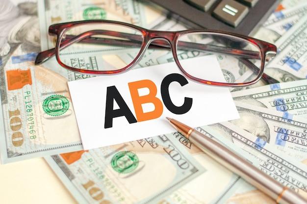 Буквы a, b и c написаны на белой карточке, лежащей на купюрах, очках, ручке и калькуляторе позади.