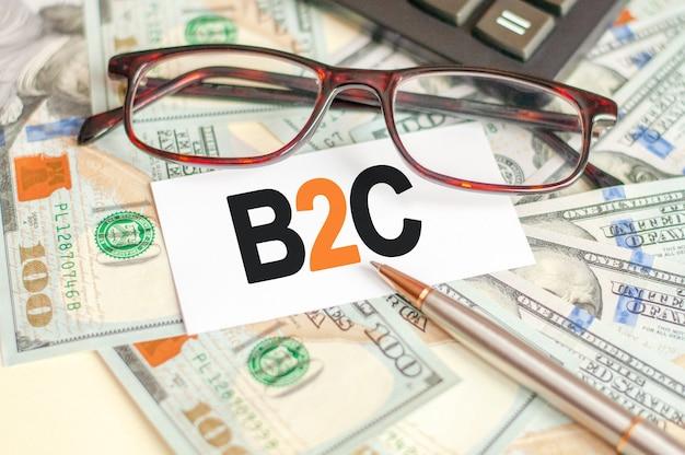 B2cの文字は、手形、眼鏡、ペン、電卓の後ろにある白いカードに書かれています