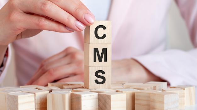 여자의 손, 분홍색 배경으로 나무 장난감 블록에 문자 cms. 비즈니스 개념. cms-content management system의 약자