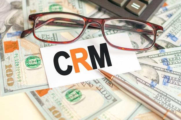 Буквы crm написаны на белой карточке, лежащей на счетах, очках, ручке и калькуляторе позади.