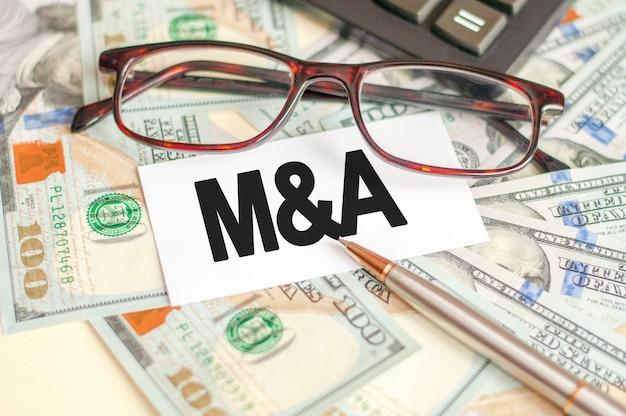 Буквы m и a написаны на белой карточке, лежащей на купюрах, очках, ручке и калькуляторе на заднем плане. m и a - слияния и поглощения. концепция бизнеса и финансов.