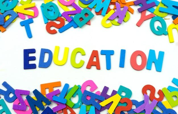합판으로 만든 편지 교육 단어는 흰색 배경에 있습니다.