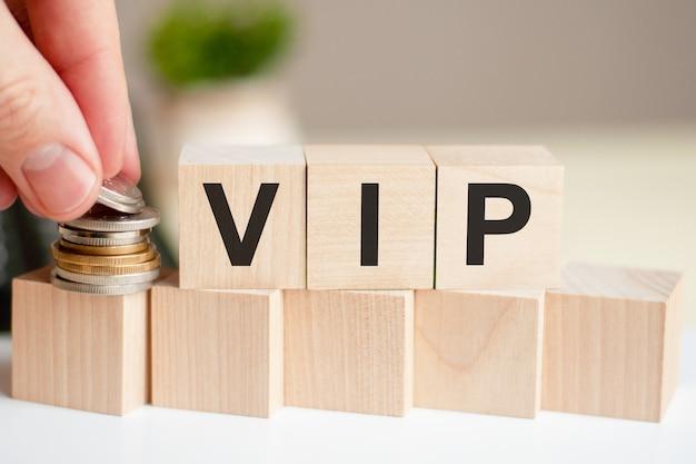 나무 큐브에 쓰여진 편지 vip. 사람의 손이 입방체 표면에 동전을 놓습니다. 비즈니스 개념.