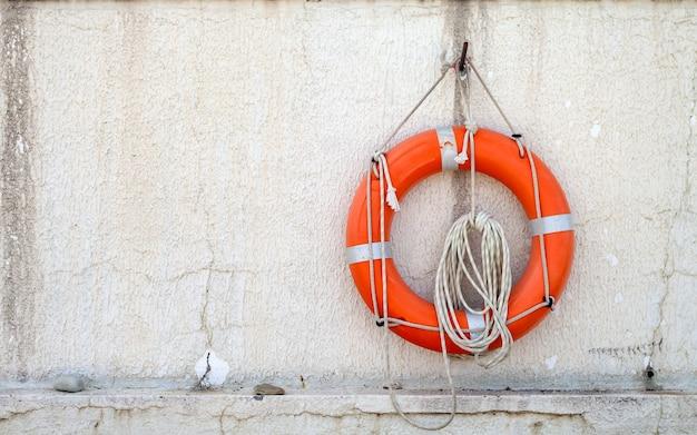 Спасательный круг со шнуром висит на бетонной стене рядом с пляжем.