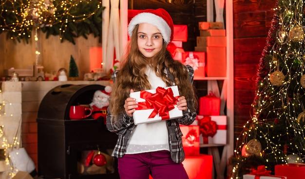 당신이 받을 자격이 있는 라이프스타일. 겨울 선물입니다. 산타클로스 모자 액세서리. 크리스마스 이브. 크리스마스 축 하에 대 한 준비 패션 소녀입니다. 꼬마 패셔니스타. 세련된 작은 아이. 메리 크리스마스. 놀라다.